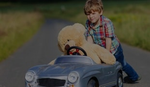 Child in childs car with teddy