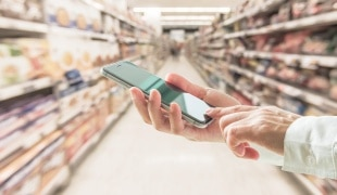 Person holding phone in supermarket aisle